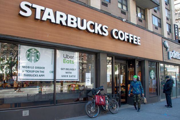 A delivery rider wearing a protective mask picks up an order from Starbucks on April 28 in New York City....