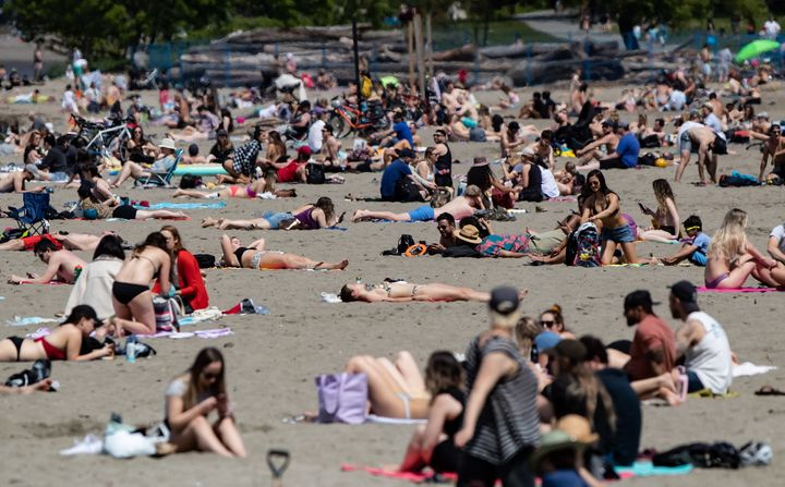 People sun themselves at Vancouver's Kitsilano Beach as temperatures reached into the range of 20 C, according to Environment Canada on May 10, 2020.