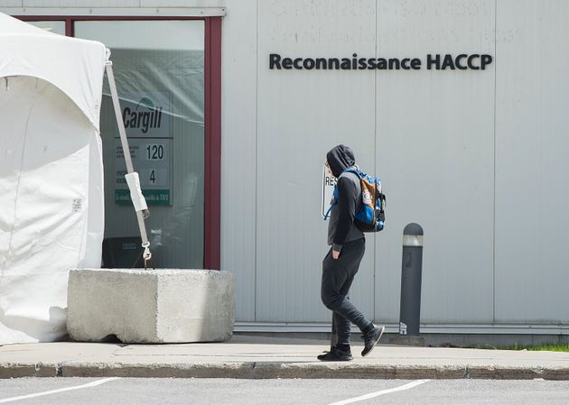 A man walks into a Cargill meat processing factory in Chambly, Que., south of Montreal on