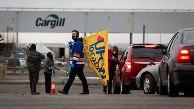 A union representative greets workers returning to the Cargill beef processing plant in High River, Alta....