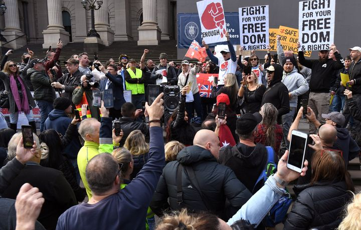 Anti-lockdown protesters chant on the steps of Victoria's state parliament in Melbourne on May 10, 2020 before police arrested 10 protesters - Hundreds of people gathered to protest the state's tough lockdown laws as well as 5G, vaccinations and coronavirus being a hoax.