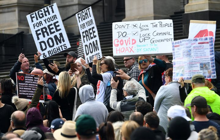 Anti-lockdown protesters hold placards on the steps of Victoria's state parliament in Melbourne on May 10, 2020 before police arrested 10 protesters - Hundreds of people gathered to protest the state's tough lockdown laws as well as 5G, vaccinations and coronavirus being a hoax.
