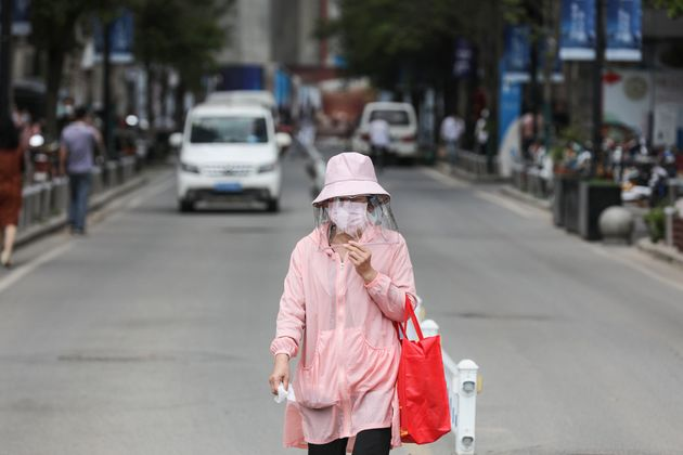 A woman wears a face shield as she walks along a street in Wuhan in China's central Hubei province on...