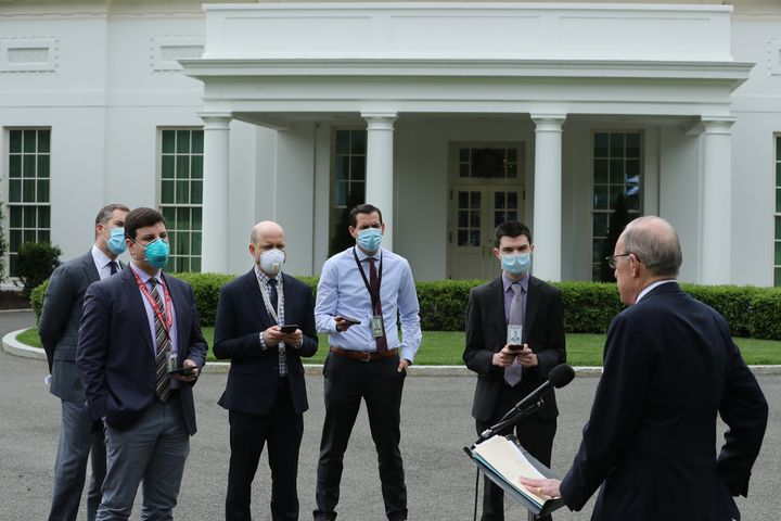 White House Economic Council Director Larry Kudlow, who was not wearing a mask, briefs masked reporters outside the White Hou
