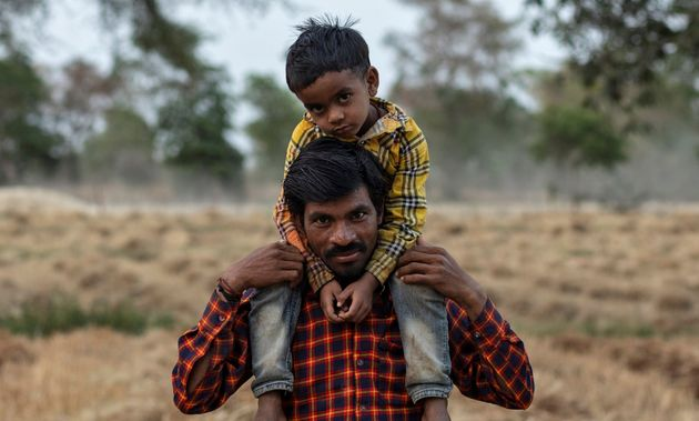Dayaram Kushwaha, a migrant worker, with his 5-year-old son, Shivam, after he returned to his home from...