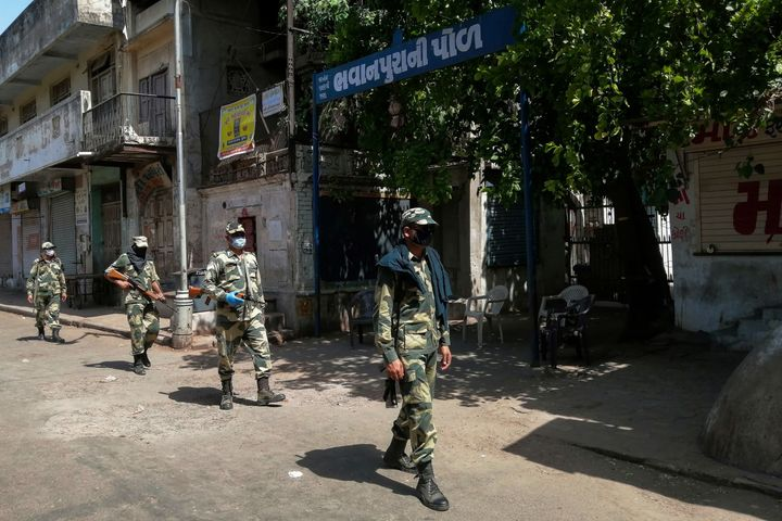 Border Security Force (BSF) soldiers patrol along a street during a government-imposed lockdown in Ahmedabad on May 8, 2020.