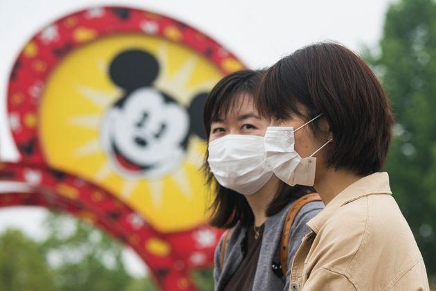 Dos turistas en Disney Town, junto a Disneyland, en Shanghai (China) el 5 de mayo de 2020 (Hu Chengwei/Getty