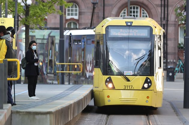Commuters wait to board a tram in Manchester, after prime minister Boris Johnson said people who cannot...