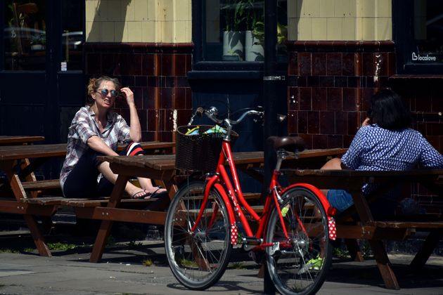 Two women sit outside a closed pub on Saturday as Britain faces its seventh week of