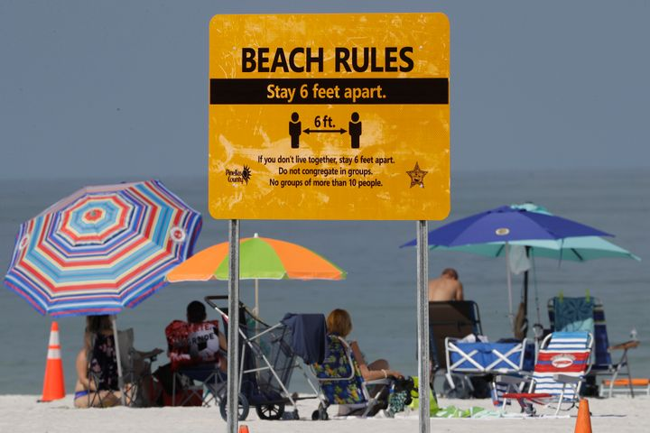 Beachgoers sunbathe near a beach rules sign after Clearwater Beach officially reopened to the public on May 4, in Clearwater