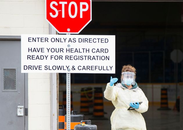 A medical worker directs a vehicle at a drive-thru COVID-19 testing centre in Hamilton, Ont., on April...