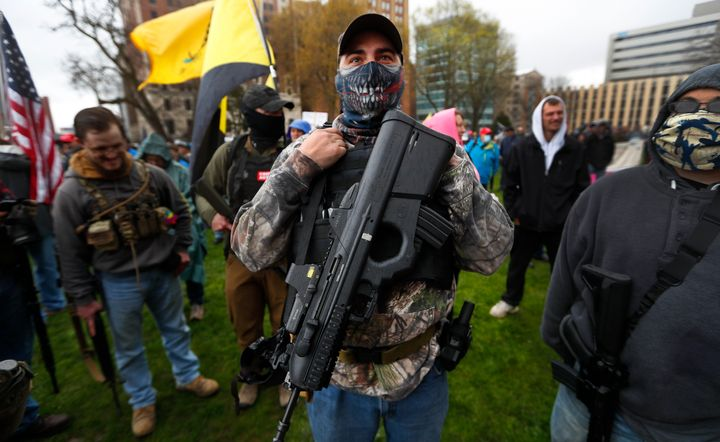 A protester carries his rifle at the state Capitol in Lansing, Michigan, on April 30, 2020. Hoisting U.S. flags and handmade