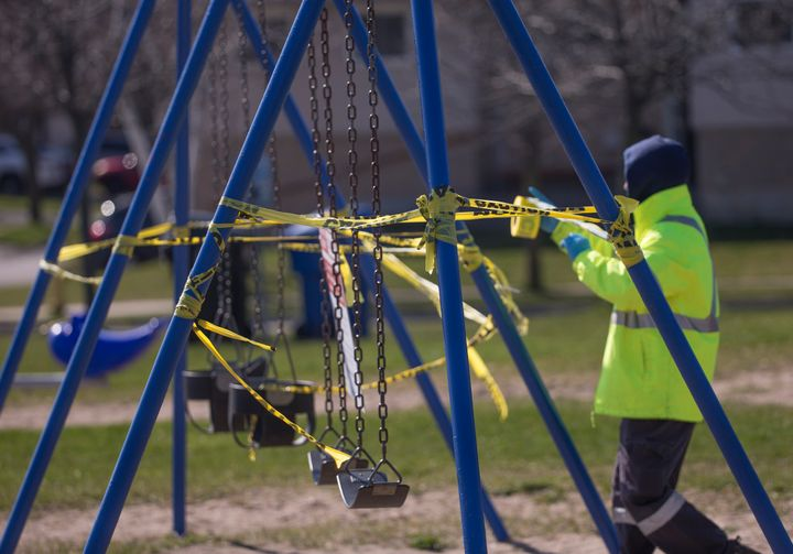 A City of Toronto employee reinstalls caution tape that was torn off a swing set on April 27, 2020.