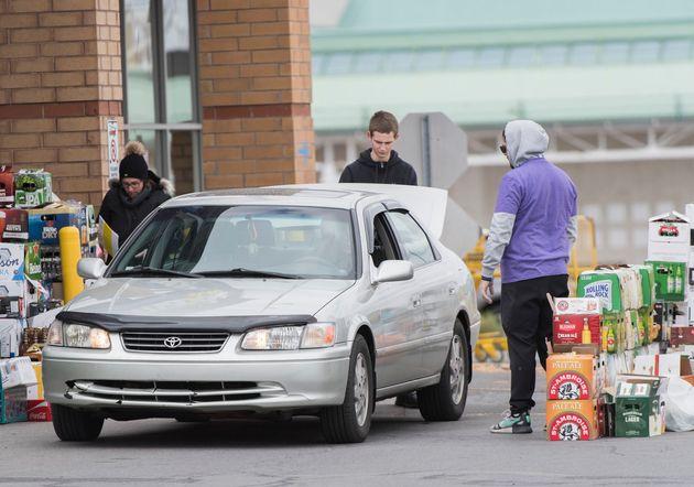 Les gens déposent leurs bouteilles et canettes à l'entrée d'une épicerie Maxi de la banlieue montréalaise...