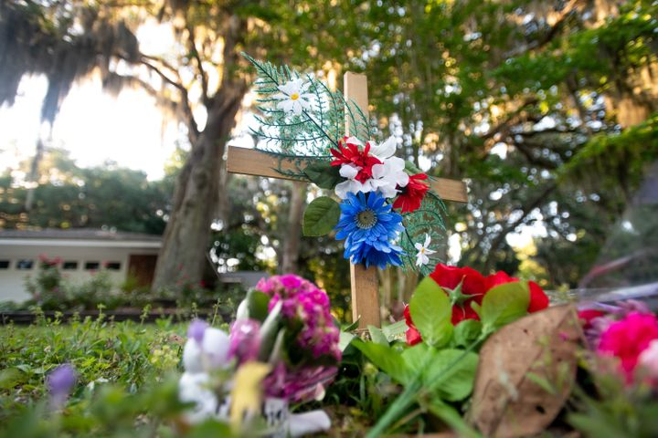 A cross and flowers are placed Thursday near the intersection where Ahmaud Arbery was fatally shot in the Satilla Shores neig