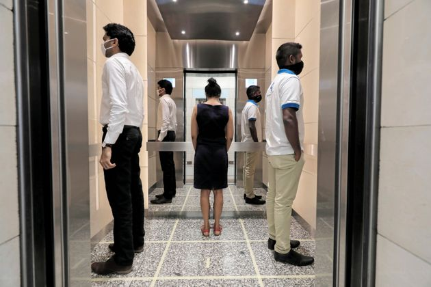 People practice social distancing inside an elevator in Colombo, Sri Lanka, on May