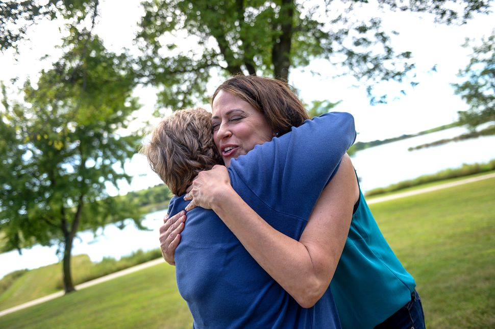 Theresa Greenfield hugs an attendee at a Democratic Party picnic this past August. Everywhere she goes, people come forward w