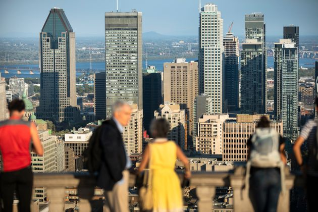 In this file photo, people stand atop the Mount Royal lookout above downtown Montreal, Aug. 23,