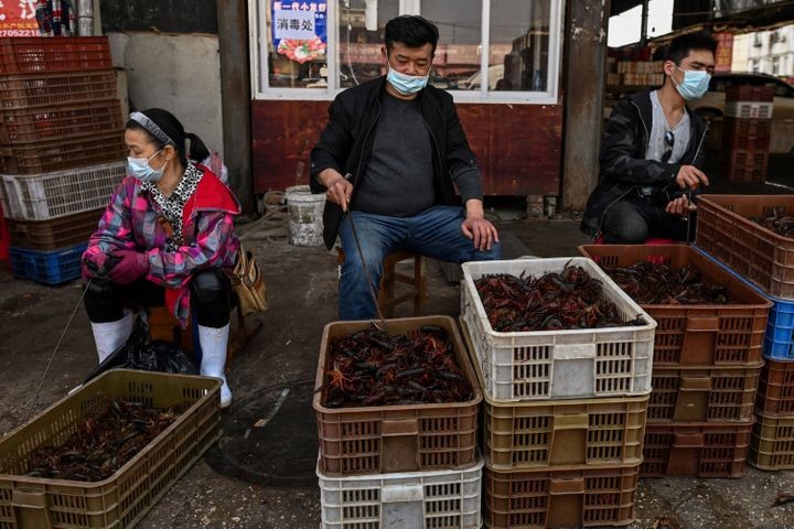 Vendors wear face masks as they offer prawns for sale at the Wuhan Baishazhou Market in Wuhan in China's central Hubei province.