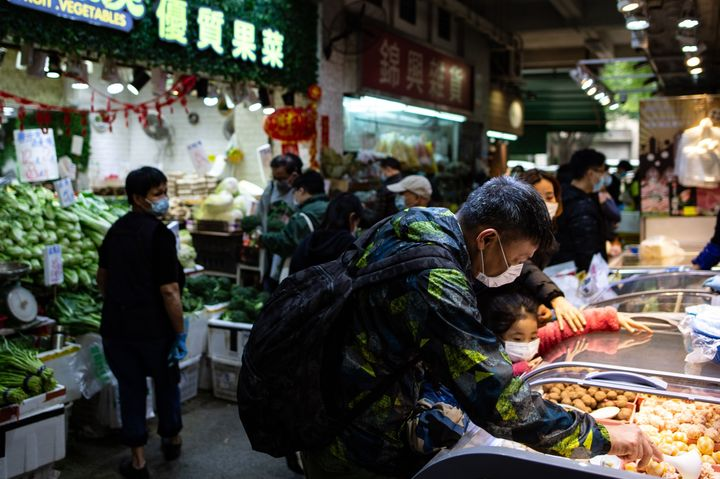 People shopping at a wet market as residents in Mei Foo in Hong Kong.