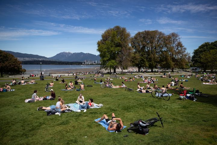 People sit and lie in the sun at Kitsilano Beach Park as temperatures reached high into the 20s in Vancouver on May 9, 2020.