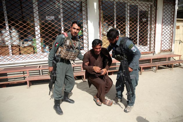 Afghan policemen comfort a man after an attack on a maternity hospital, in Kabul, Afghanistan, Tuesday,...