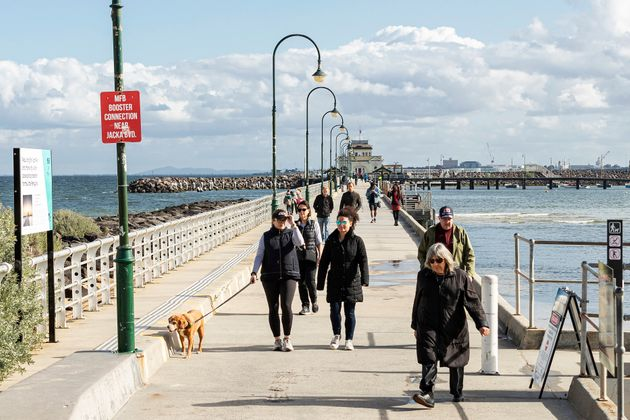 People walk along St Kilda Pier on May 13, 2020 in Melbourne, Australia. COVID-19 restrictions have eased slightly for Victorians in response to Australia's declining coronavirus (COVID-19) infection rate.