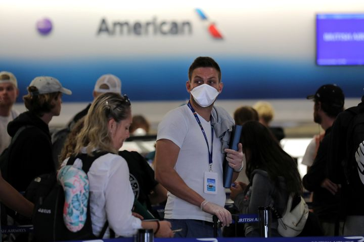 A passenger wearing a mask waits in line to check in for a flight at Miami International Airport in Miami, Florida, on March