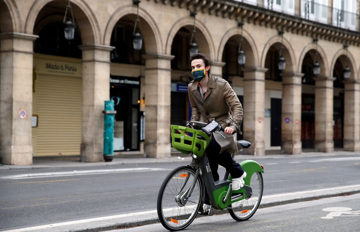 "A man wearing a face mask rides a Velib bicycle in the deserted and car-free ""rue de Rivoli"" in Paris, France, on May 5."