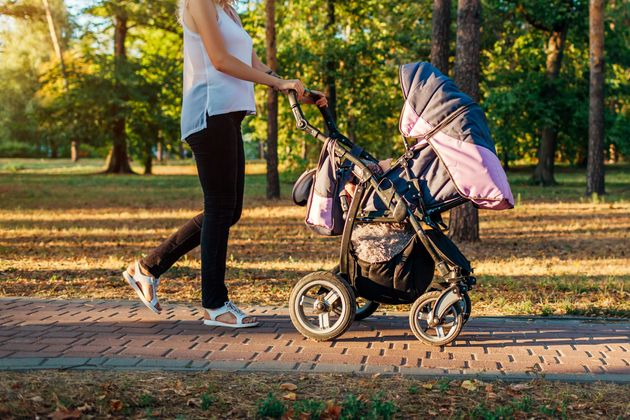 Mother's day. Young woman walking in spring park with baby carriage. Mother spends time with her toddler...