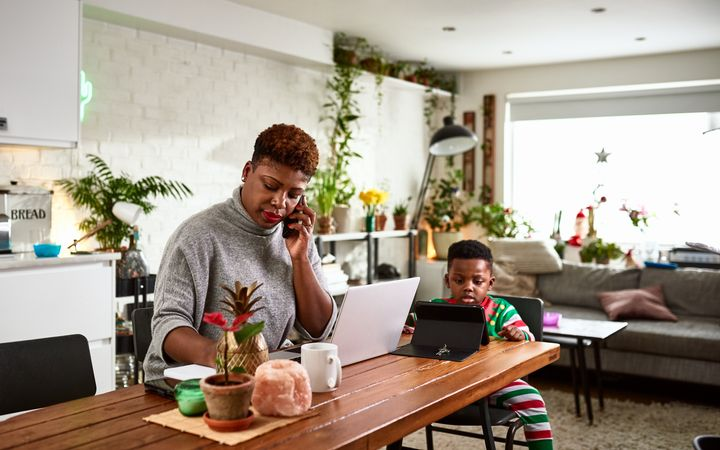 A multi-tasking mother looks after her young son while working from home in this undated stock photo.