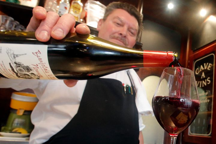 A bartender pours a Beaujolais Nouveau wine just outside of Paris. It's a ritual to uncork Beaujolais Nouveau on the third Thursday of every November.