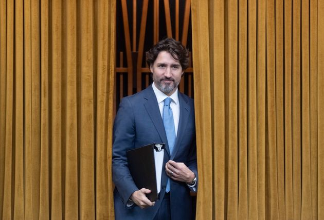 Prime Minister Justin Trudeau walks through the curtains before a session of the Special Committee on...