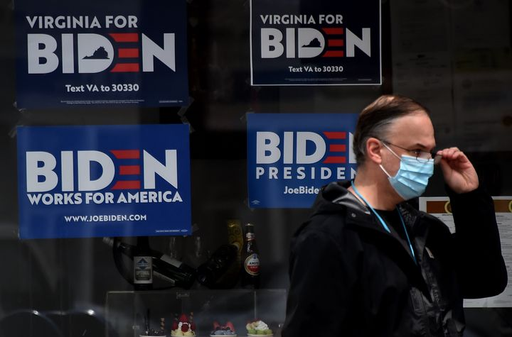 A man wearing a face mask walks past signs Monday in Alexandria, Virginia, for Joe Biden's 2020 presidential campaign amid th