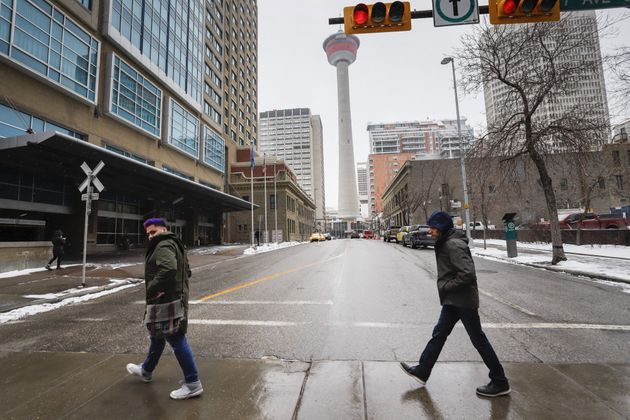 Pedestrians cross a quiet street in downtown Calgary on Mar. 18, 2020, amid a worldwide COVID-19