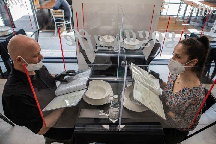 Μιλάνο, Δεύτερο Στάδιο: Εστιατόριο ετοιμάζεται να καλωσορίσει πελάτες. Στα τραπέζια υπάρχει διαχωριστικό πλεξιγκλάς. Στη φωτογραφία είναι δυο εργαζόμενοι που κάνουν πρόβα για την σωστή απόσταση.