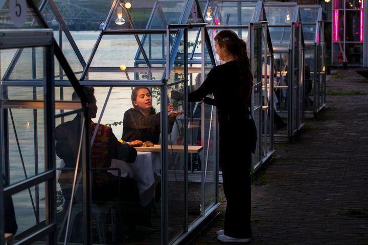 Το προσωπικό στο εστιατόριο Mediamatic σερβίρει φαγητό σε εθελοντές που κάθονται σε μικρά γυάλινα σπίτια σε εξωτερικό χώρο, στην πρόβα λίγο πριν την επαναλειτουργία.