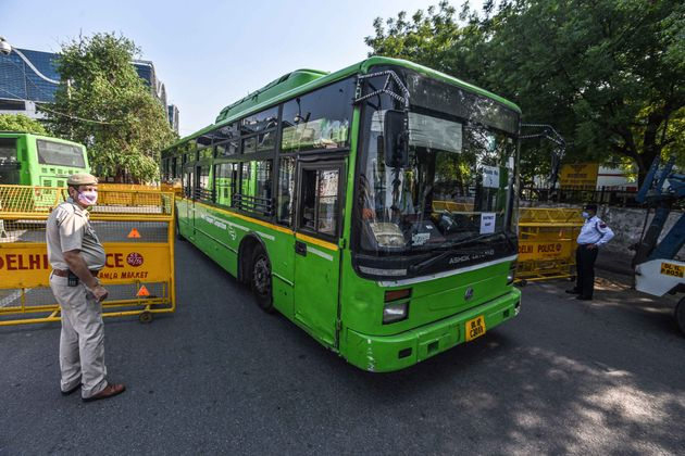 Delhi Police personnel stand guard as a bus reaches New Delhi Railway Station on May 7,