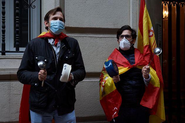 Dos personas participan en las movilizaciones del madrileño barrio de