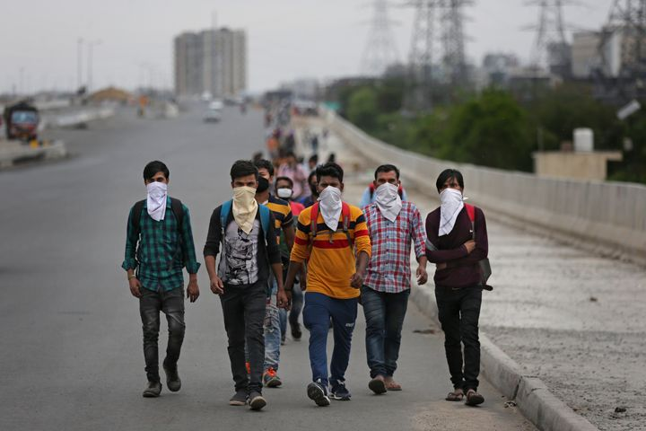 A group of daily wage labourers walk along an expressway on the outskirts of New Delhi on March 26, 2020.
