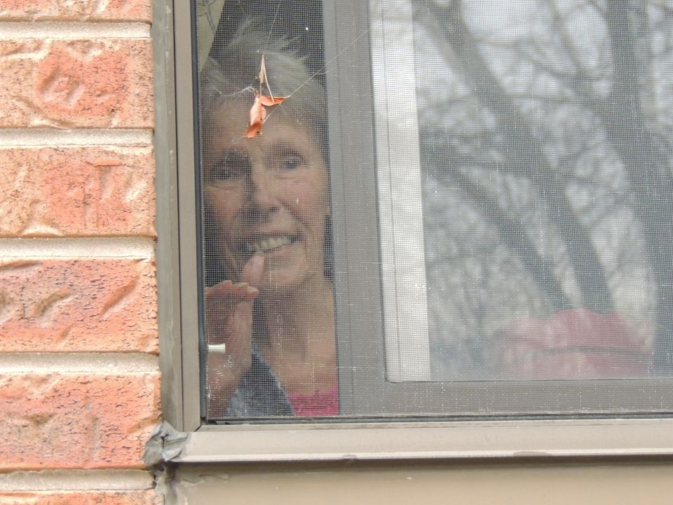 In an undated photo, Martha Grace waves to her daughter Brenda Shepherd through a window at Forest Heights Long Term Care in Kitchener, Ont.