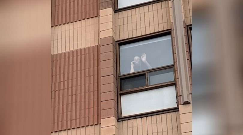 Christine Collins' brother Peter waves from his room at Carlingview Manor on April 30,