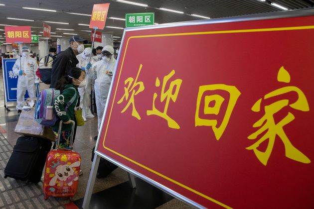 Passengers from Wuhan walk past a sign that reads