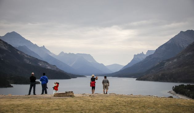 Tourists look out over Waterton Lake at Waterton National Park, Alta., on Aug. 9,