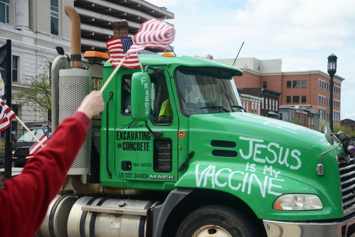 "A truck bearing the message ""Jesus is my vaccine"" blares its siren in support while passing anti-quarantine and pro-Trump pro"