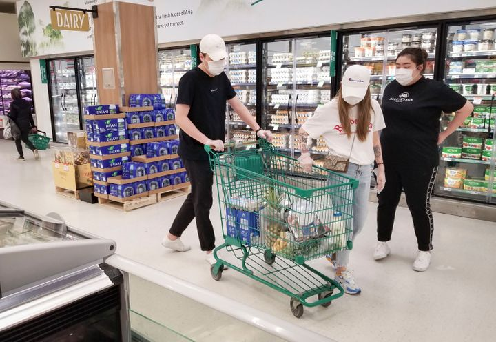 People wearing face masks shop at a Vancouver grocery store.