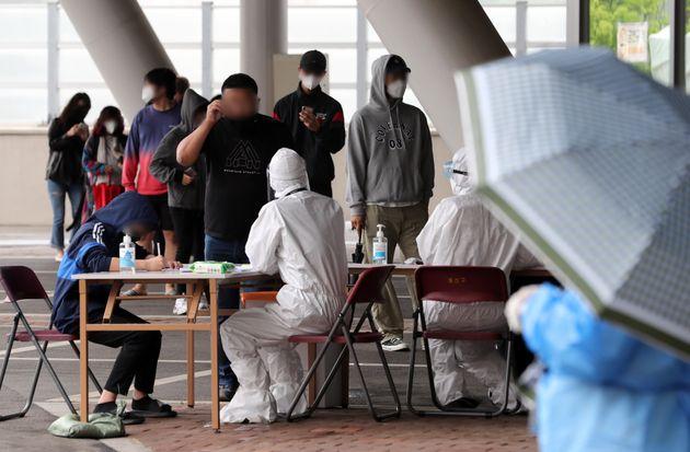'이태원 클럽발' 신종 코로나바이러스 감염증(코로나19)이 확산되고 있는 15일 오전 서울 용산구 한남동 공영주차장에 마련된 도보형 이동형(워킹스루) 선별진료소를 찾은 시민들이 문진표...