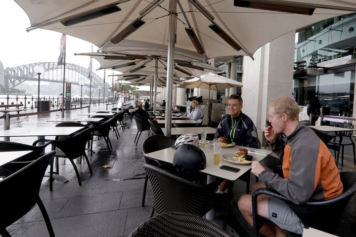 Rob Barton, right, and Charlie Downe have lunch at a restaurant along the shoreline as stage 1 of the lifting of COVID-19 restrictions begin in Sydney, Friday, May 15, 2020. Some pubs, clubs and restaurants are reopening with a limit of 10 patrons while following distancing guidelines.