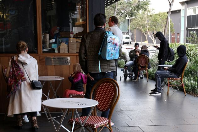 Customers sit at a cafe on the first morning of eased coronavirus disease (COVID-19) restrictions, allowing...