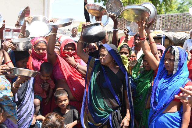 Migrant labourers and families from Bihar and Uttar Pradesh states hold kitchen utensils as they protest...